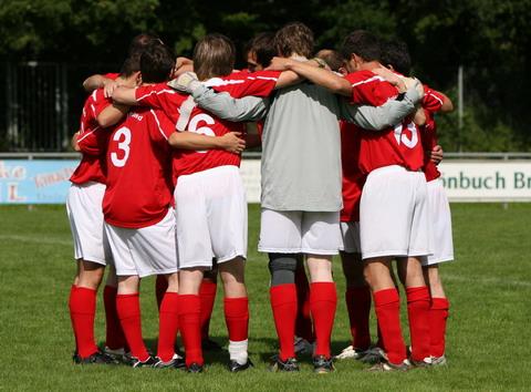 Junge Fussball-Mannschaft umarmit sich im Kreis
